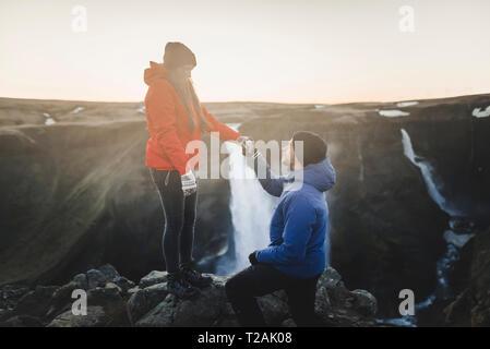 Jeune homme propose à sa petite amie lors d'une randonnée par Haifoss cascade en Islande Photo Stock