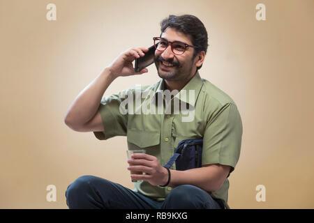 Smiling man wearing eyeglasses de conversations au téléphone mobile tout en tenant une petite pochette dans une main et un verre de thé dans l'autre. Photo Stock