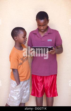 Sept et onze ans, frères du Rwanda jouer avec un ipad. Photo Stock