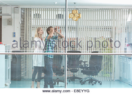 Smiling man and woman looking out window Photo Stock