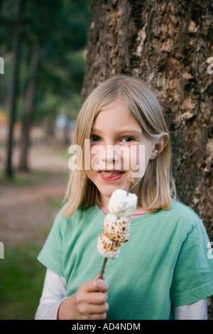 Une jeune fille manger de la guimauve grillée Photo Stock