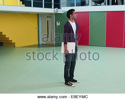Man holding laptop in empty office Photo Stock