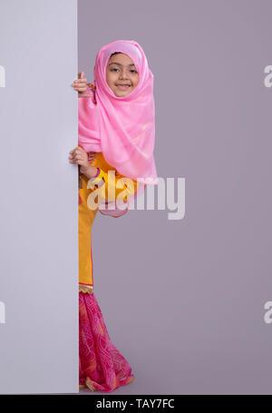 Jeune musulmane avec hijab peeking de derrière le mur et smiling Photo Stock