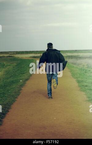 Homme d'âge moyen s'exécutant dans l'espace littoral rural Photo Stock