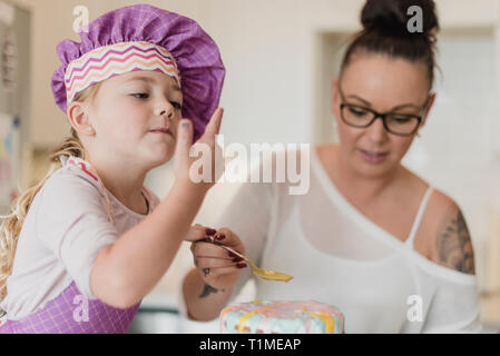 Mère et fille decorating cake Photo Stock
