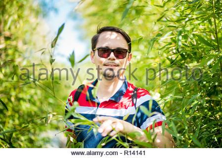 Portrait d'un jeune homme portant des lunettes de soleil Photo Stock