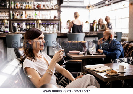 Souriant, confident businesswoman drinking wine in bar Photo Stock