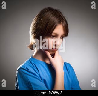 Portrait d'un garçon en bleu haut de la pensée. Photo Stock