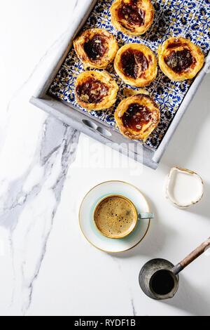 Tarte aux oeufs traditionnels portugais dessert Pasteis de nata Pastel en tuile classique plateau avec tasse de café noir et pot de lait sur le marbre blanc background Photo Stock