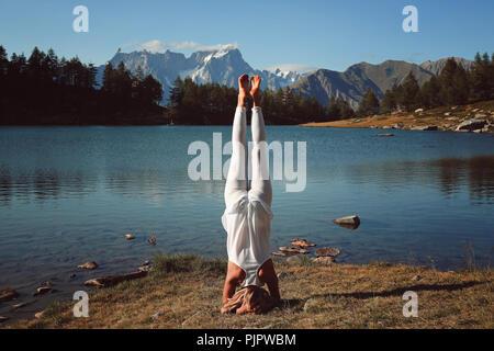 Woman practicing yoga at lakeshore. La lumière au coucher du soleil Photo Stock