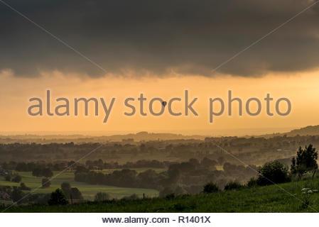 Un ballon à air chaud au-dessus d'un champ pendant le coucher du soleil Photo Stock