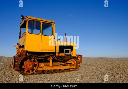 Tracteur jaune rouillé sur weybourne beach, North Norfolk, Angleterre Photo Stock