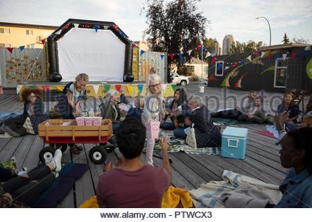 Girl selling popcorn de foule en attente de film en parc pour commencer Photo Stock