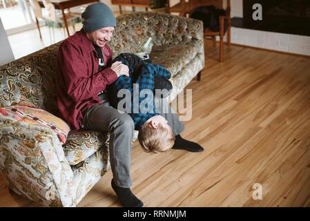 Père ludique holding fils envers sur salon canapé Photo Stock