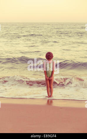 Girl in swimcap debout dans les vagues Photo Stock