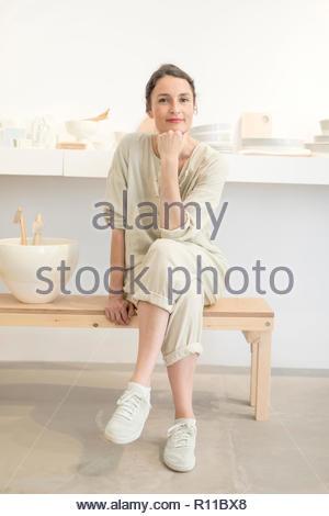 Portrait of a smiling young woman sitting at home à la recherche dans l'appareil photo Photo Stock