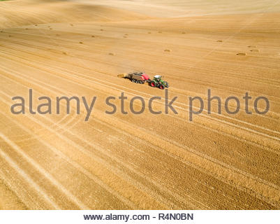Vue aérienne de la ramasseuse-presse du tracteur en bottes de paille dans les champs après la récolte du blé à la ferme en été Photo Stock