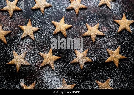High angle close up de cookies en forme d'étoiles saupoudrés de sucre glace sur fond noir. Photo Stock