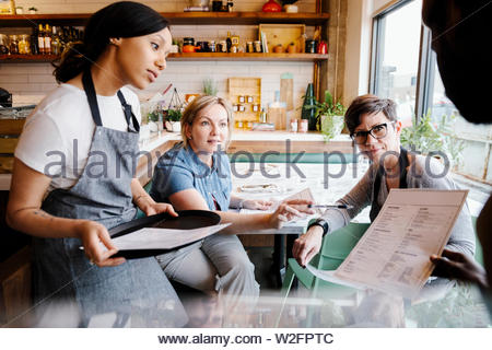 Manager et serveurs discutant dans menu cafe Photo Stock