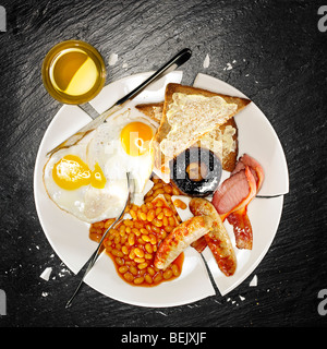 Un petit-déjeuner complet contenant des œufs, saucisses, bacon, fèves au lard, champignons et pain grillé Photo Stock
