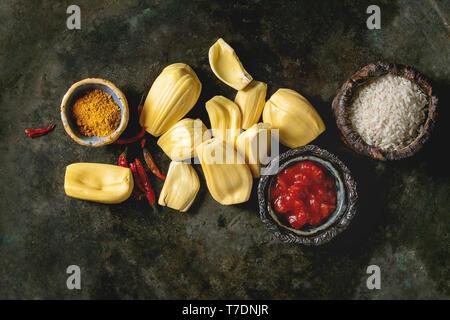 Ingrédients pour la Cuisine vegan curry. Matières premières mûres pelées jaque avec blanc riz non cuit, les tomates hachées et les épices dans des bols en céramique sur dark metal Photo Stock