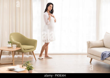 Cheerful pregnant woman standing in living room Photo Stock