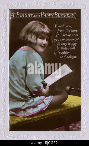 Une petite fille aux cheveux courts est assise sur un tabouret de piano, titulaires d'une carte d'anniversaire. Photo Stock