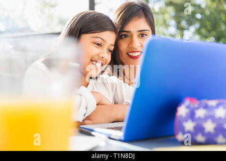 Happy mother and daughter using laptop Photo Stock