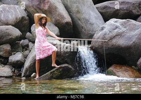 Fille de la campagne de pêche dans une rivière de montagne. Amusement et relax Photo Stock
