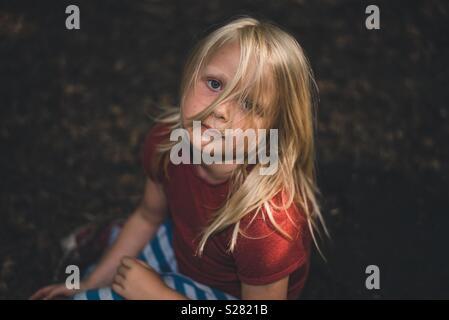 Enfant assis dans les bois Photo Stock