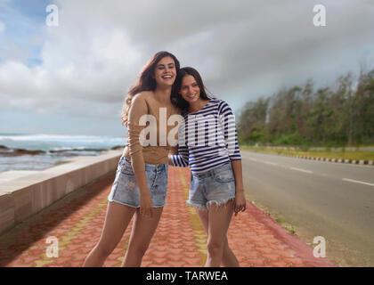 Deux femmes se tenant debout sur la mer à côté de la route se tenant Photo Stock