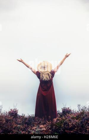 Une femme dans une robe rouge avec un chapeau est raising her arms Photo Stock