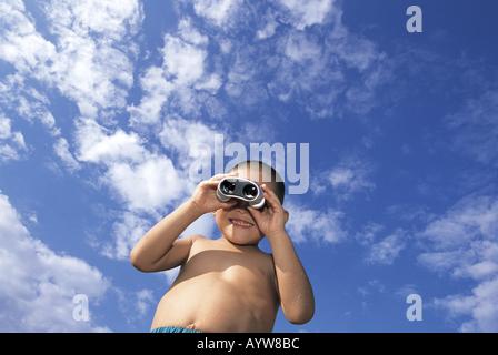 Garçon à la recherche de jumelles avec ciel bleu en arrière-plan Photo Stock
