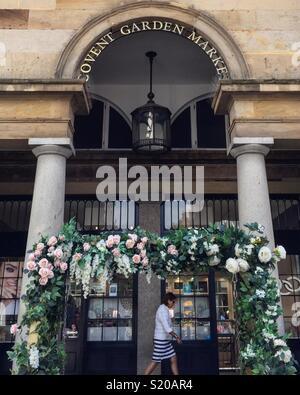 Femme sous un porche fleuri à Covent Garden Photo Stock