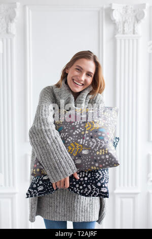 Smiling woman holding coussins à motifs Photo Stock