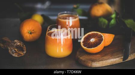 Verres de jus d'orange fraîchement pressé ou sang smoothie sur comptoir de cuisine en béton, close-up. Mode de vie sain, végétarien, végétalien, régime alimentaire, l'alcaline Photo Stock