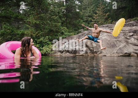Jeune homme enjoué avec anneau gonflable sauter dans le lac à distance, Squamish, British Columbia, Canada Photo Stock