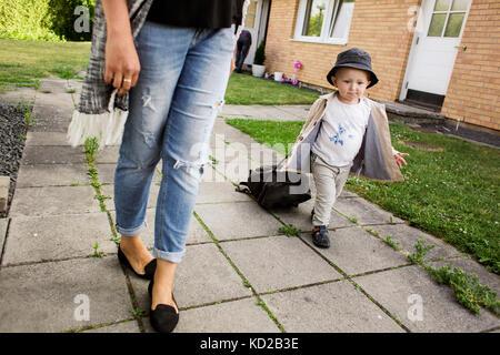 Mère marcher avec son (18-23 mois) sur le trottoir Photo Stock