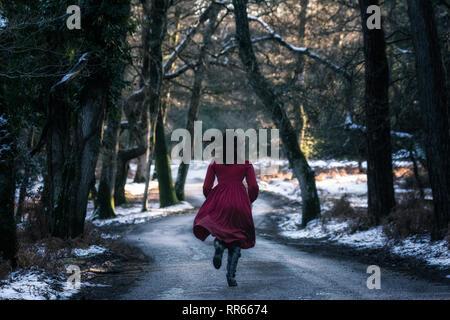 Une jeune femme en robe rouge sur une petite rue au coeur d'une forêt hiver avec de la neige Photo Stock