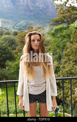 Portrait of young woman standing dans le balcon à la maison Photo Stock