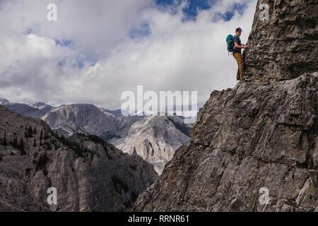 L'homme à l'escalade de montagne escarpée, abrupte face Photo Stock