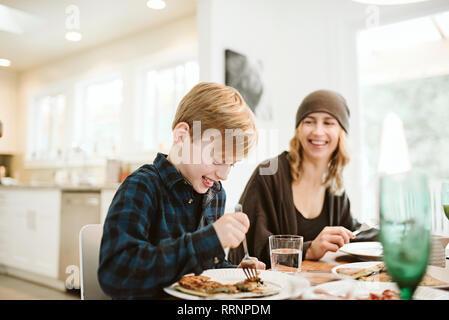 La mère et le fils de manger le petit déjeuner aux crêpes à table Photo Stock