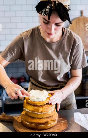 Un cuisinier travaillant dans une cuisine commerciale de l'assemblage d'un gâteau en couches avec la crème fraîche. Photo Stock