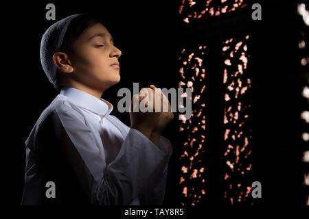 Jeune garçon musulman wearing cap priant dans le noir avec les yeux fermé Photo Stock