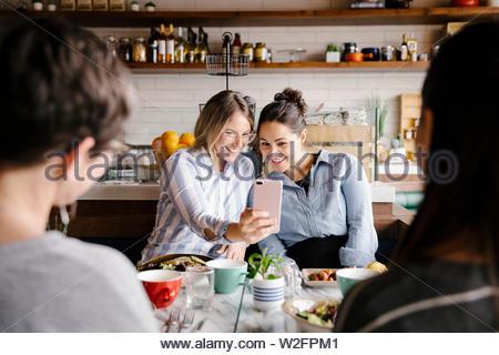 Heureux les jeunes femmes friends avec selfies smart phone in cafe Photo Stock