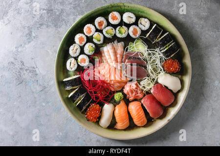 Set à Sushi nigiri sashimi et sushi rolls dans une assiette en céramique avec salade sur fond de béton gris. Mise à plat, de l'espace. Menu Japon Photo Stock