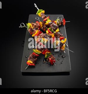 Brochettes de boeuf et de légumes sur les brochettes, sur un fond noir. Photo Stock
