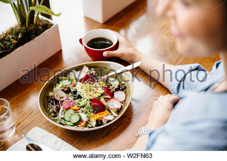 Woman eating salad in cafe Photo Stock