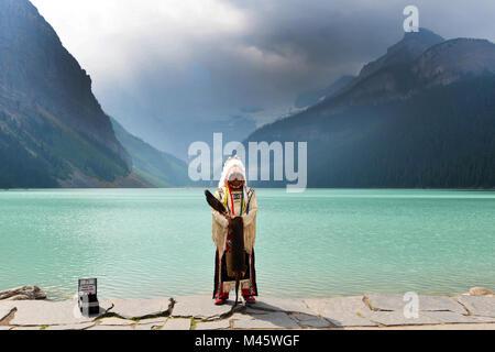 Une Première Nation native Canadian homme pose pour photos touristiques au lac Louise, Canadian Rockies Photo Stock