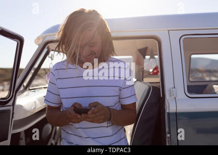 Vue avant du happy young man using mobile phone while standing against van at beach Photo Stock